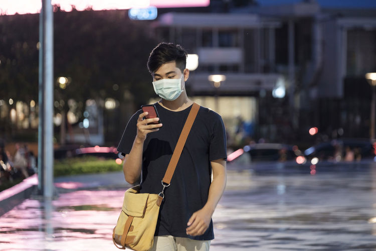 Young man wearing mask using phone standing on road