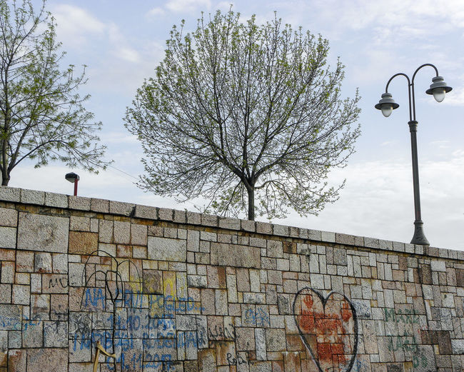 Low angle view of graffiti on wall against sky