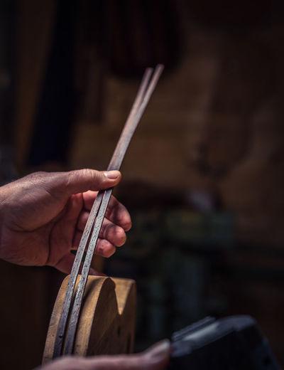 Cropped hand holding sticks in darkroom