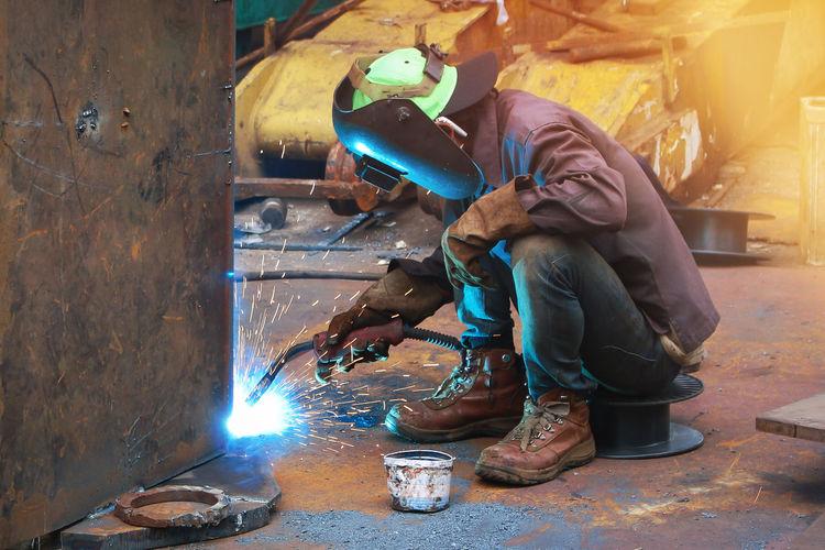 Side View Of Welder Welding Metal In Factory