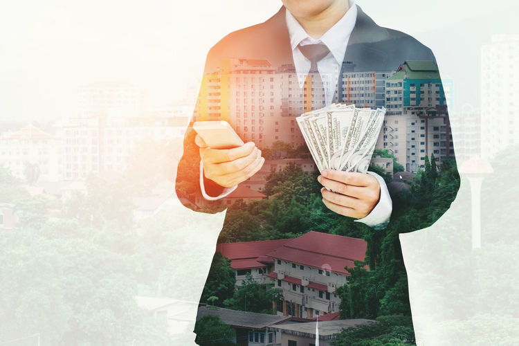 Double Exposure Of Businessman Holding Paper Currency And Mobile Phone Against City