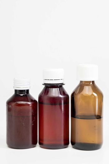 Bottle of medicine Healthcare And Medicine White Background Studio Shot Bottle Indoors  Medicine Container Glass - Material Copy Space Cut Out No People Group Of Objects Science Still Life Close-up Three Objects Red Choice Food And Drink Herbal Medicine