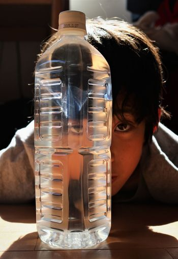 Close-Up Portrait Of Boy With Water Bottle On Table