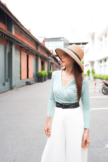 Young woman wearing hat standing against built structure