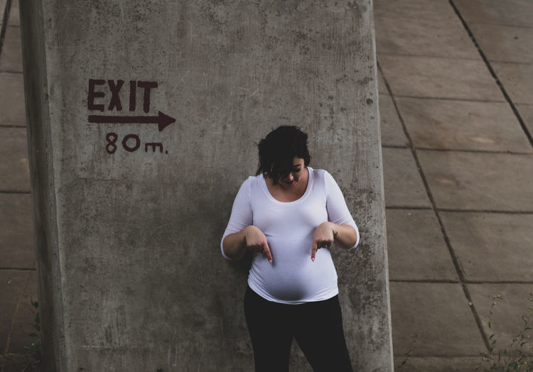 Pregnant woman showing stomach while standing against wall