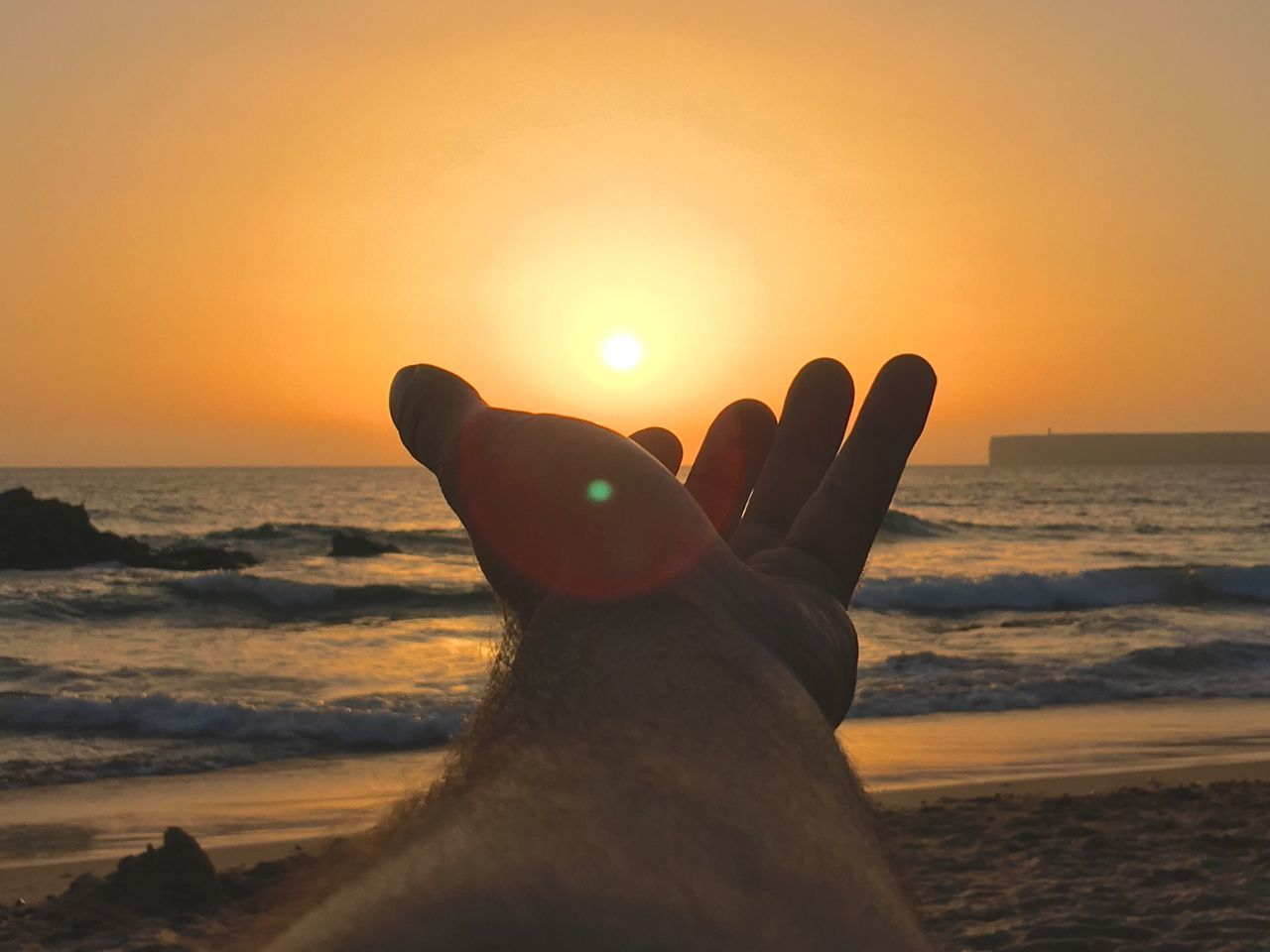 sunset, sea, human body part, sun, human hand, horizon over water, one person, sky, water, beach, real people, nature, beauty in nature, sunlight, outdoors, silhouette, close-up, scenics, day, people