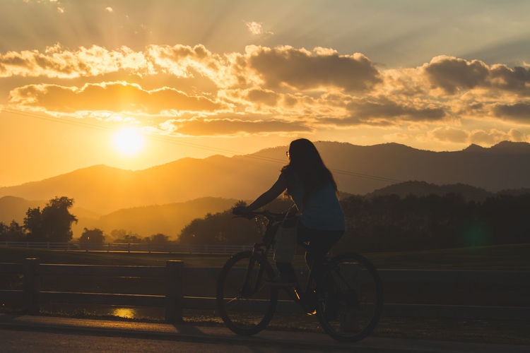 Woman Cycling On Street Against Mountains During Sunset