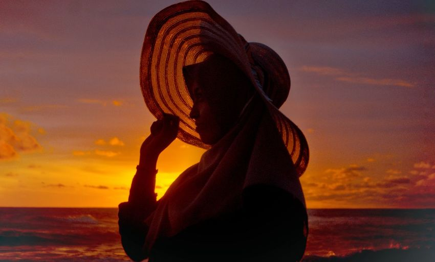 Woman looking at sea during sunset