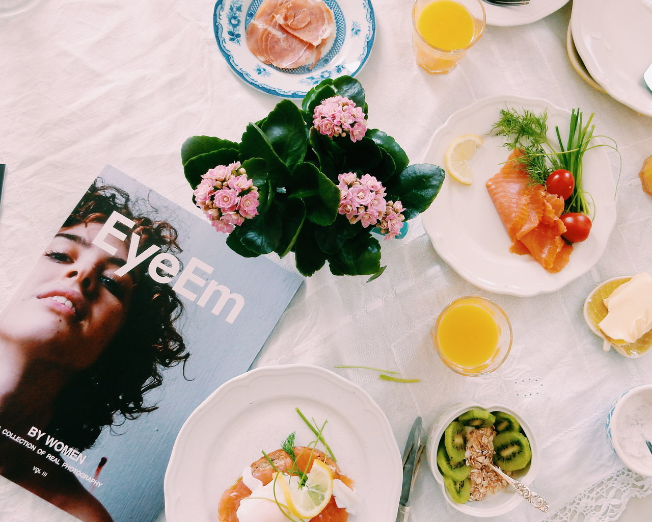 Directly above shot of food on table by flower vase and magazine