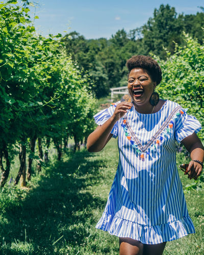 Smiling woman walking at vineyard