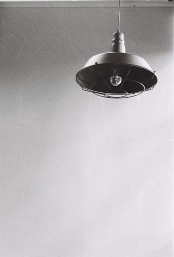 Low angle view of pendant light hanging on wall