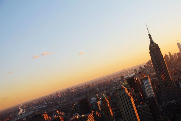 Empire state building with cityscape against sky during sunset