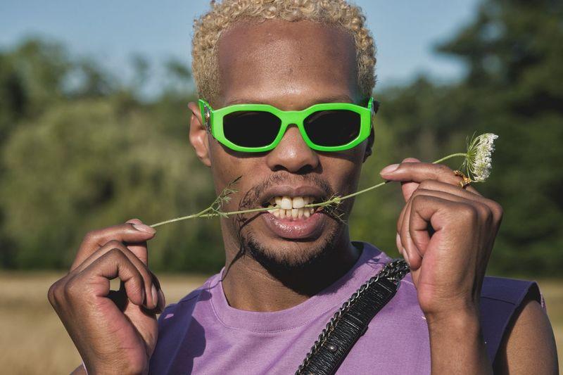 Portrait of man holding sunglasses