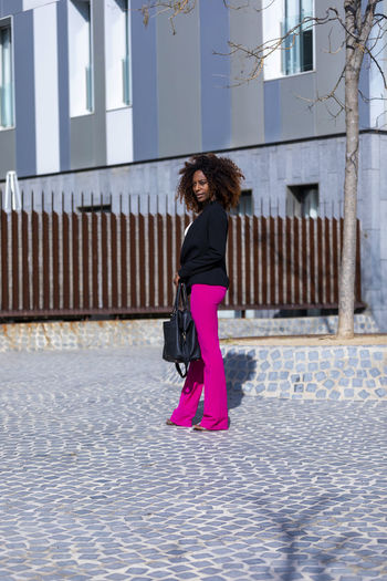 Front view of a young beautiful curly woman wearing elegant clothes and handbag while standing in the street in sunny day Architecture One Person Building Exterior Full Length Built Structure Standing Real People Women Day City Lifestyles Building Side View Clothing Fashion Street Casual Clothing Young Women Leisure Activity Outdoors Beautiful Woman Hairstyle Young Adult Woman African American Curly Hair Afro Denim Happiness Happy Fun Daylight Sunlight