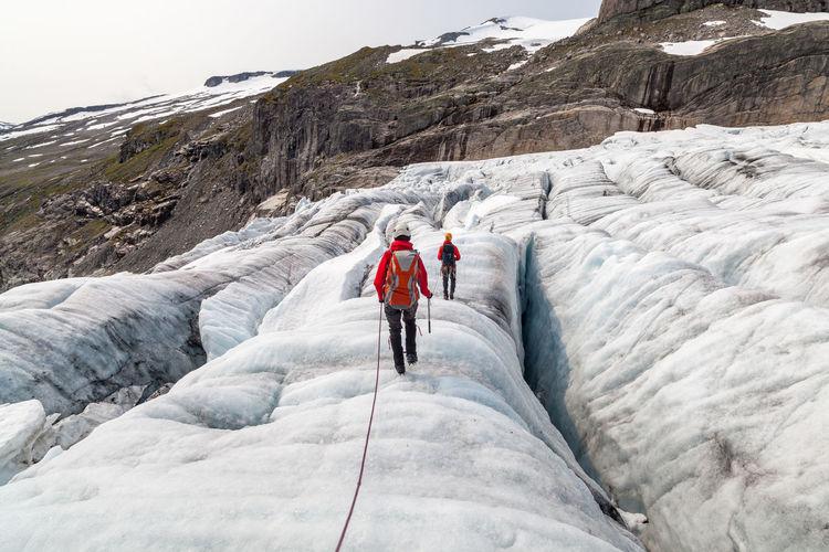 Rear view of people walking on glacier