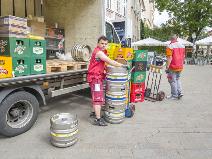 ZAGRED, CROATIA - MAY 10, 2017: Worker unloading material from lorry Boy Drink Equipment Hensem Labour Lorry Man Manual Shift Staff Supplier Supply SUPPORT Transportation Unloading Work