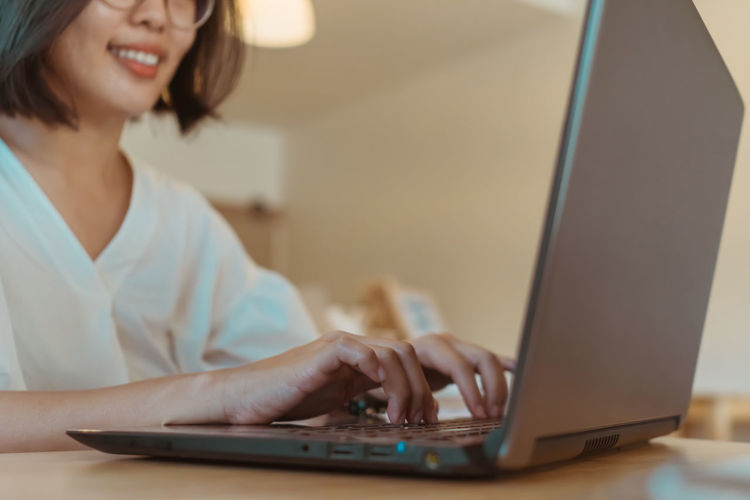 Midsection of woman using laptop while sitting on table