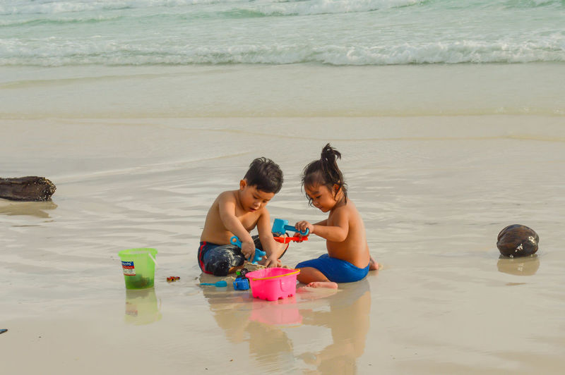 Children playing with toy on beach