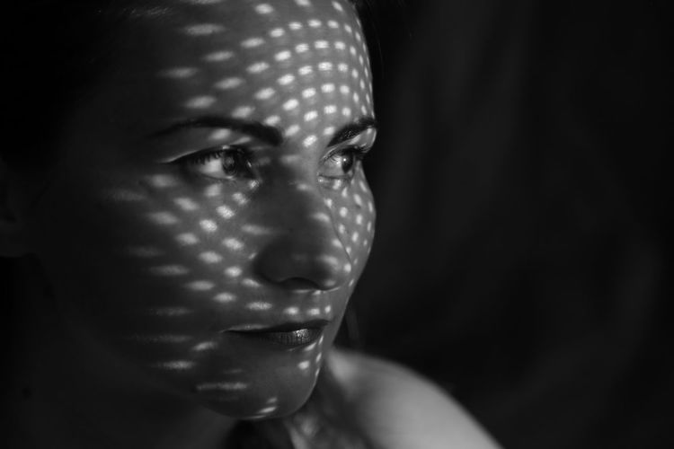 Close-up of thoughtful woman with spotted light looking away in darkroom
