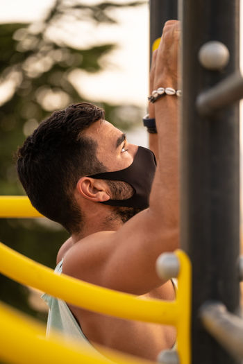 Side view of young man exercising outdoors