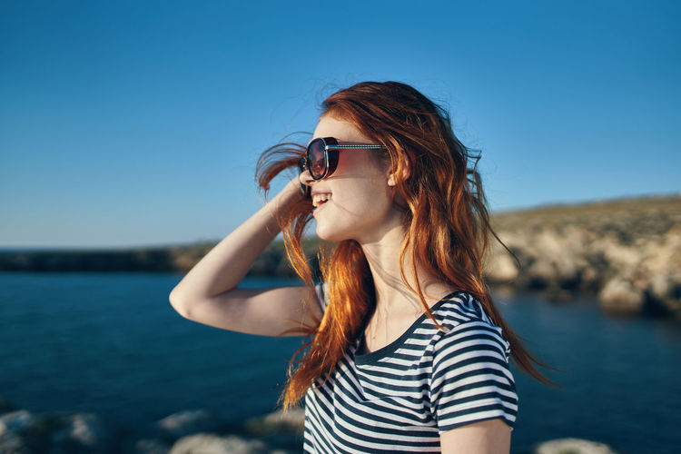 Young woman wearing sunglasses against sea against sky