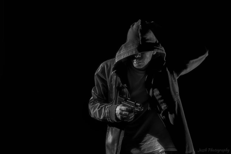 Man holding gun while wearing hooded shirt against black background