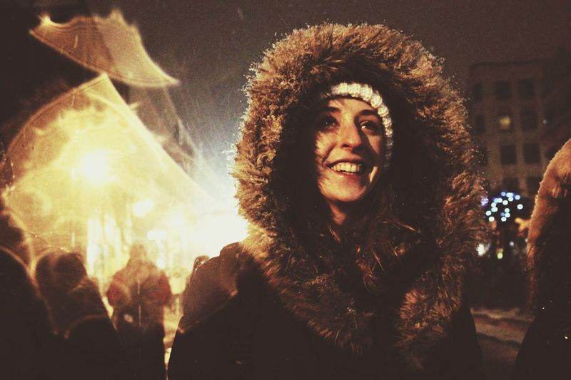 Cheerful Woman Wearing Fur Hood In City At Night