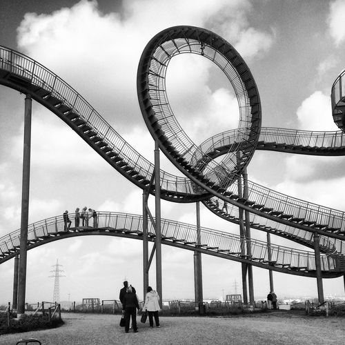 People looking at and climbing the rollercoaster-like art installation Tiger and Turtle Architecture Art Installation Arts Culture And Entertainment Black And White Built Structure Cloud - Sky Day EyeEmNewHere Industrial Landmark Leisure Activity Low Angle View Man Made Structure Monochrome Outdoors People Real People Rollercoaster Sculot Sky Staircase Tiger And Turtle Travel Destinations Urban