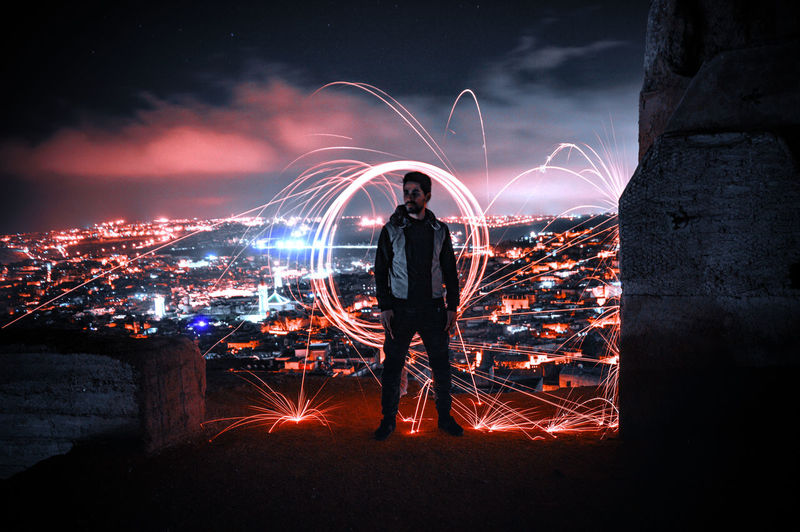 Person with light painting against sky at night