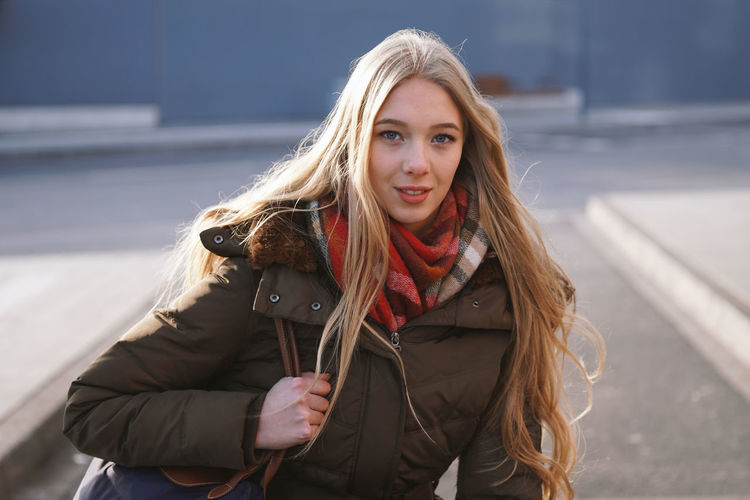 One Person Blond Hair Long Hair Young Women Real People Young Adult Lifestyles Warm Clothing Winter Scarf Outdoors Teenager Girl Waiting Bus Stop Station Bus Station Casual Fashion Street Looking At Camera Portrait