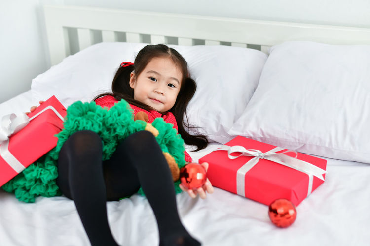Portrait Of Cute Girl Lying With Christmas Gift And Decoration In Bed At Home