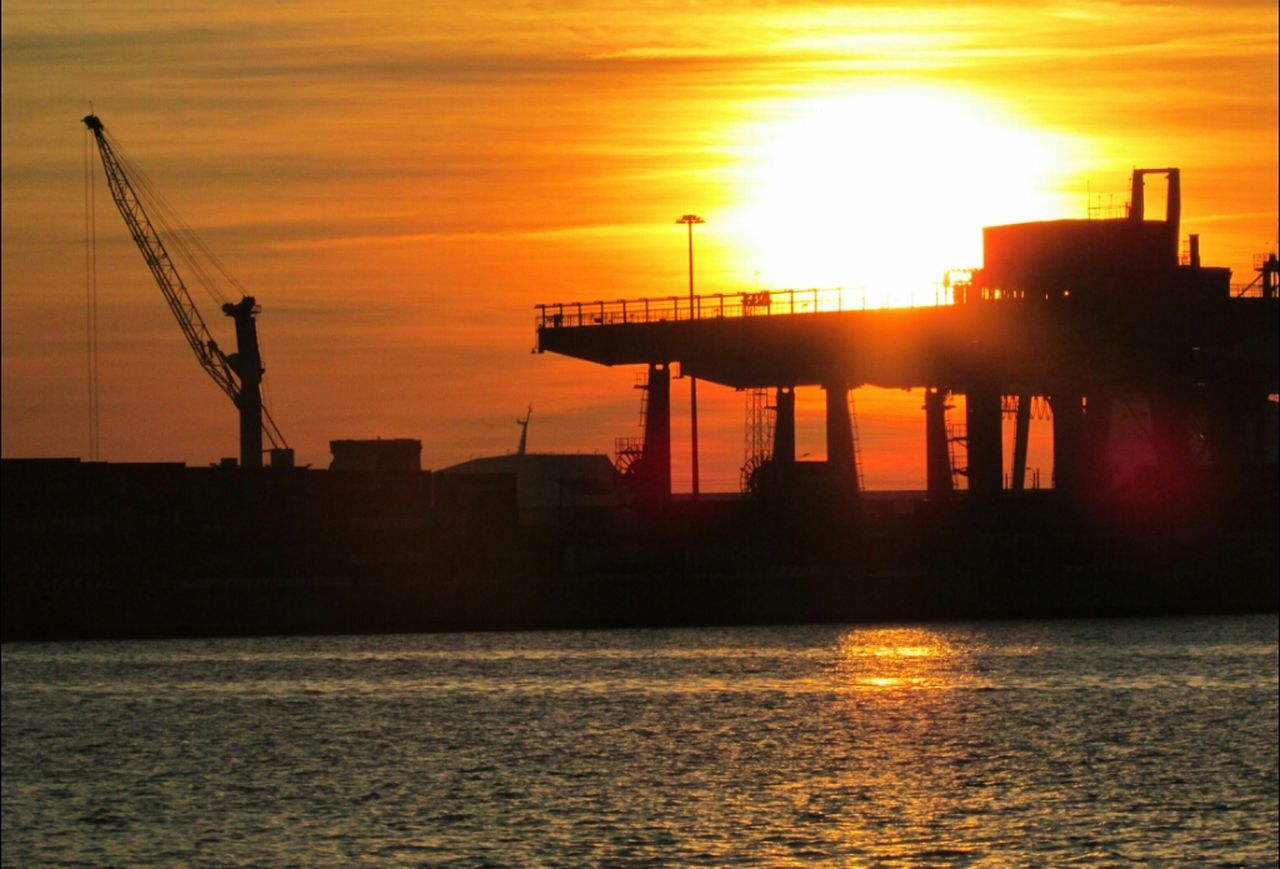 sunset, waterfront, freight transportation, silhouette, water, transportation, orange color, sun, industry, shipping, sea, sky, crane - construction machinery, mode of transport, reflection, nautical vessel, commercial dock, no people, crane, nature, architecture, outdoors, built structure, building exterior, harbor, beauty in nature, shipyard, drilling rig, day