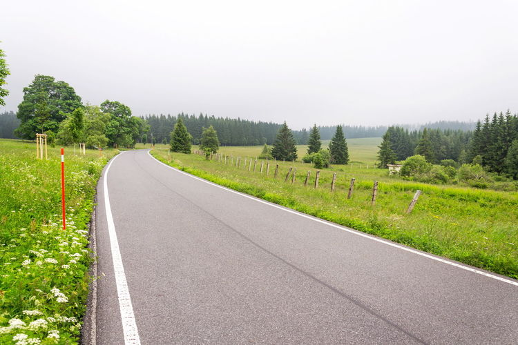 Empty road along landscape and trees against sky