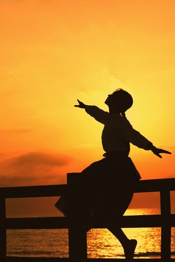 Silhouette woman with arms outstretched sitting on railing against orange sky during sunset