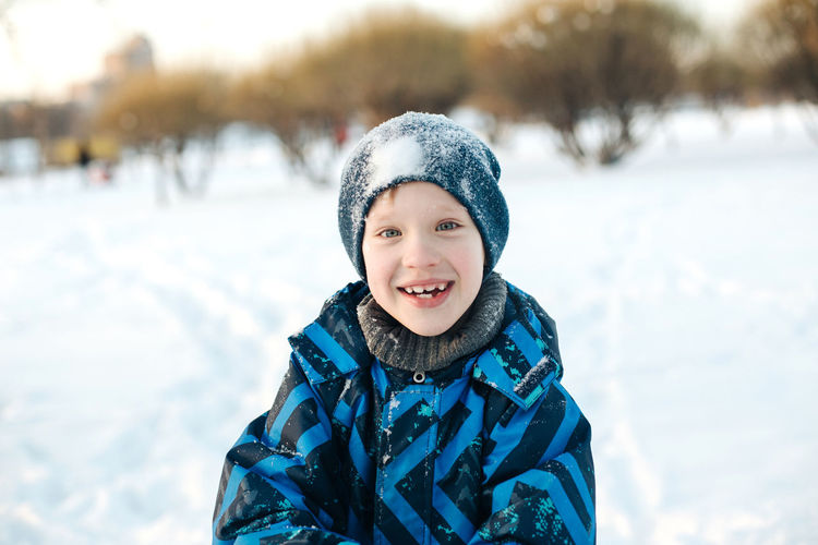 Portrait of smiling boy in snow outdoors