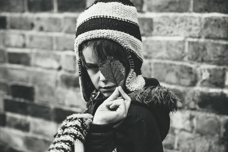 Boy In Warm Clothing Holding Leaf Against Brick Wall