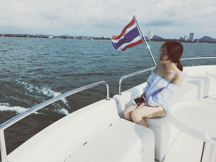 Woman traveling in boat against sky