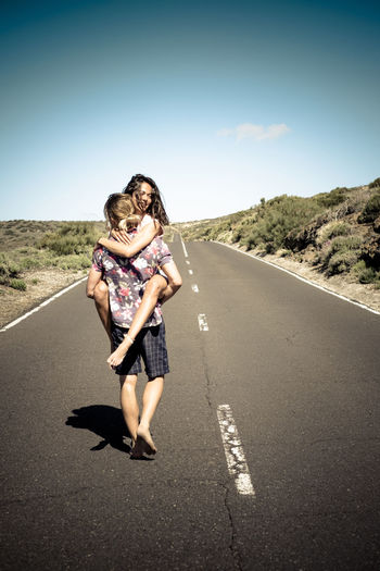 Rear view of young man carrying woman while walking on road against sky during sunny day