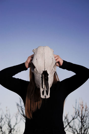Girl holding a cow skull in front of her face as a mask. Colors Halloween Horror Trees Animal Bone Animal Skull Blue Sky Clear Sky Cow Skull Creepy Day Daylight Girl Human Body Part Mask Nature One Person Outdoors People Skull Sky Spooky Mix Yourself A Good Time The Week On EyeEm