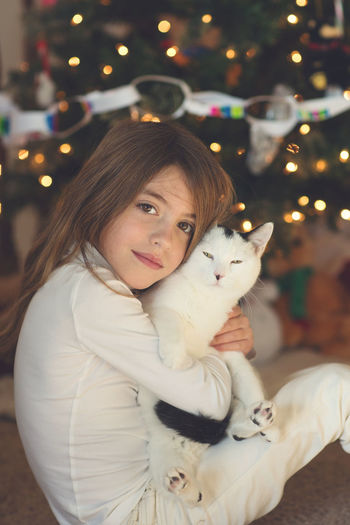 Animal Themes Cat Childhood Christmas Christmas Decoration Christmas Lights Christmas Tree Domestic Animals Focus On Foreground Happiness Home Interior Illuminated Indoors  Lifestyles Looking At Camera Mammal Night One Animal One Person Pets Portrait Real People Smiling Tree Young Adult