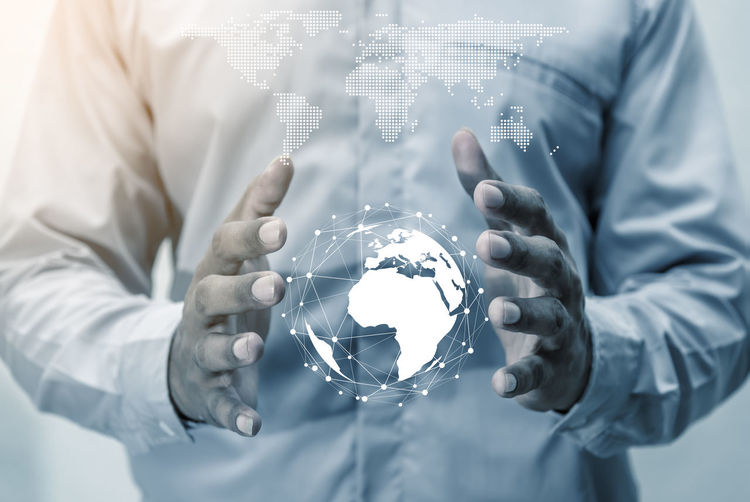 Digital composite image of businessman holding globe