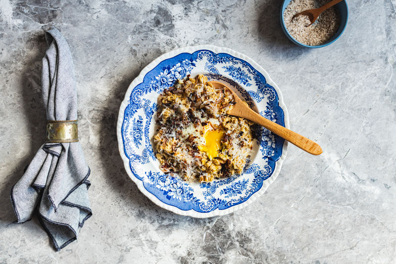 Savoury oats with poached egg, fried shallots and grated parmesan cheese