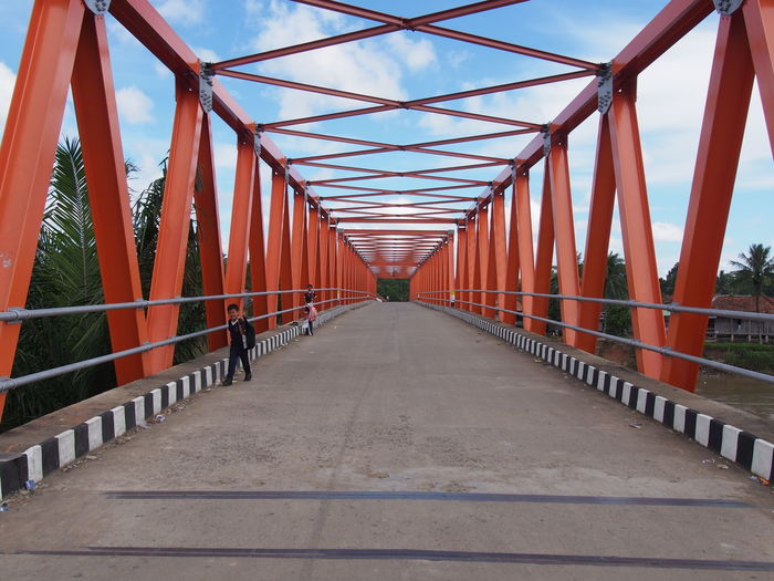 Boy Standing On Metallic Bridge Against Cloudy Sky