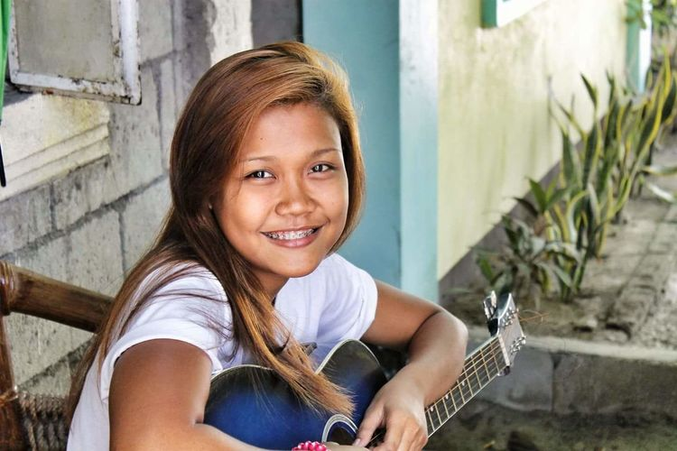 Portrait of smiling girl with guitar