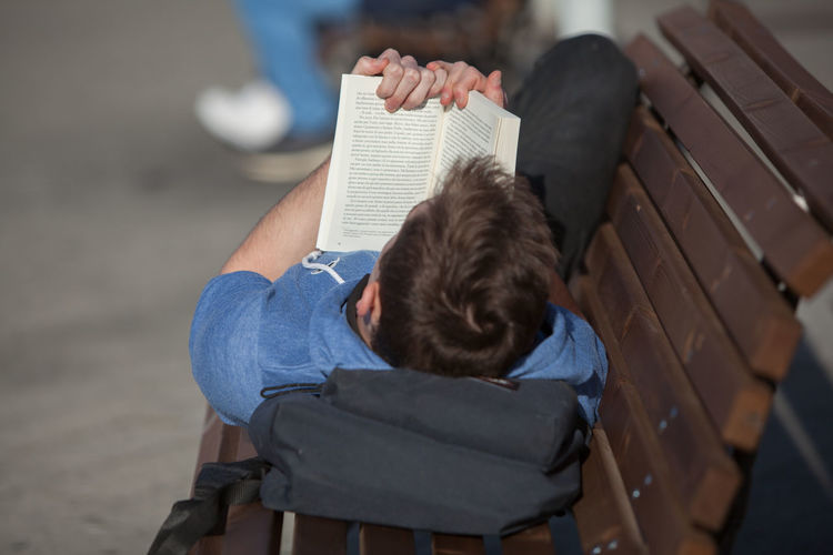 Man Reading Book While Lying On Bench At Footpath