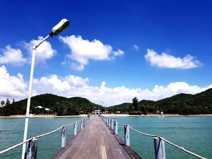 Street amidst sea against sky