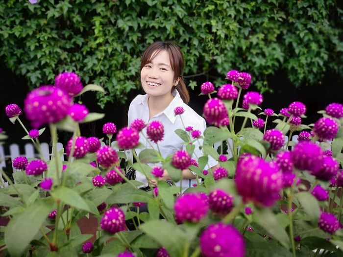 Portrait of smiling woman by pink flowers