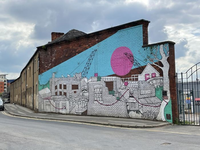 Graffiti on wall by building against sky