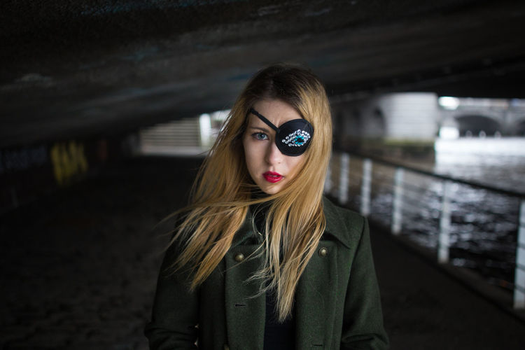 Portrait Of Young Woman Wearing Costume Eye Patch Below Bridge