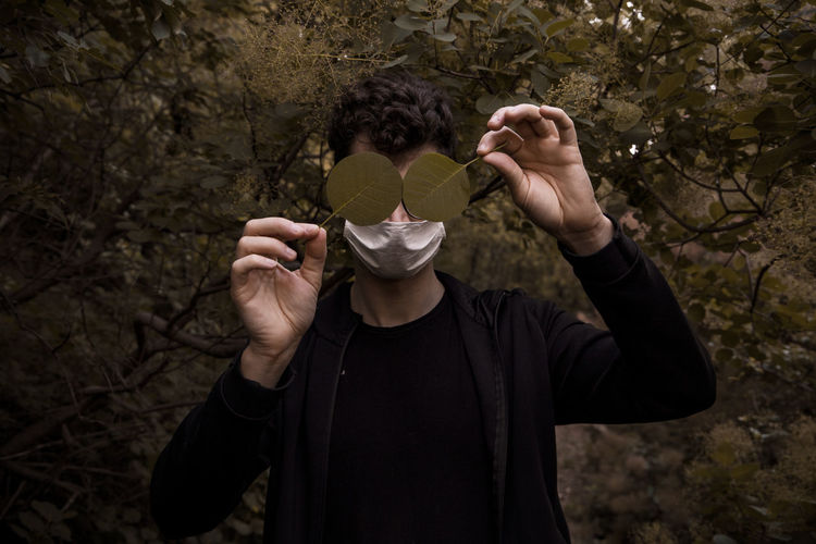 Man wearing mask holding leaves while standing against trees